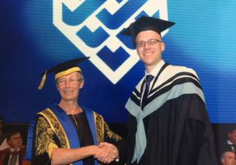 James shaking the hand of the UTS Chancellor, Professor Vicki Sara, AO